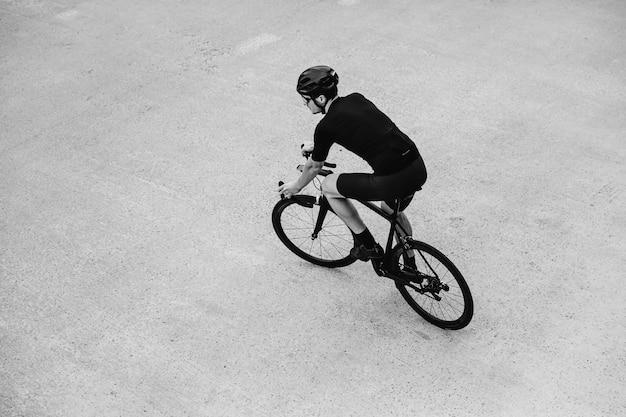 Foto em preto e branco de um homem andando de bicicleta ao ar livre
