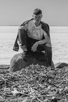 Foto em preto e branco de um homem atraente sentado à beira-mar congelado.