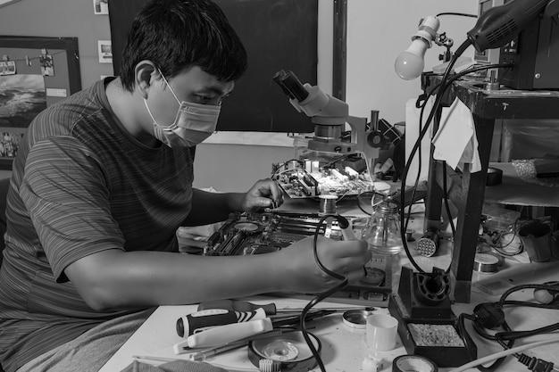 Foto em preto e branco de um reparador usando um ferro de solda quente para consertar a placa-mãe de um computador.