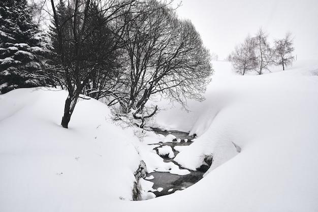 Foto em preto e branco de um riacho fluindo pela estação de esqui alpe d huez, nos alpes franceses