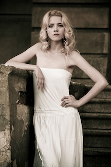 Foto em preto e branco de uma bela jovem em um vestido branco desce as escadas no fundo de um antigo prédio com portas. conceito de romance gótico