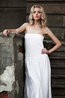 Foto em preto e branco de uma bela jovem em um vestido branco descendo as escadas no espaço de um prédio antigo com portas