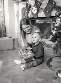 Foto em preto e branco de uma jovem mãe feliz e um bebê de 1 ano no chão sob uma árvore de natal na sala de estar