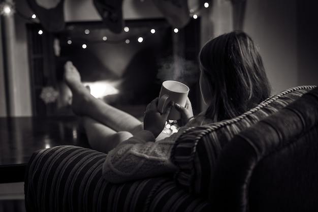 Foto em preto e branco de uma linda mulher sentada à lareira com uma xícara de chá
