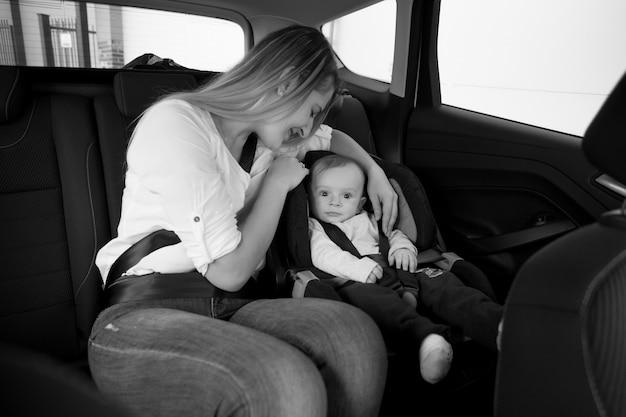 Foto em preto e branco de uma mãe sorridente sentada no banco de trás do carro com seu bebê