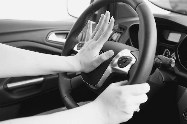 Foto em preto e branco de uma mulher buzinando no trânsito