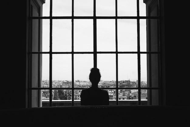 Foto em preto e branco de uma mulher solitária em frente às janelas, olhando para os edifícios