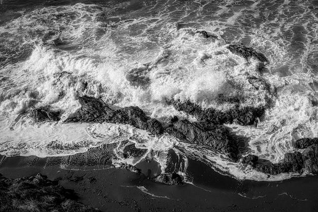 Foto em preto e branco de vista superior de um litoral coberto por rochas