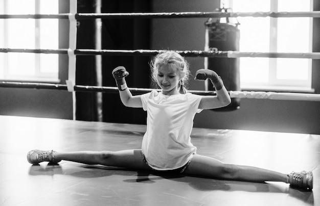 Foto em preto e branco. jovem menina com roupas esportivas está no ginásio tem dia de exercício. concepção de boxe.