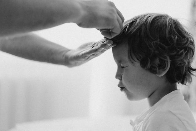 Foto em preto e branco. pai corta o cabelo do filho no quarto