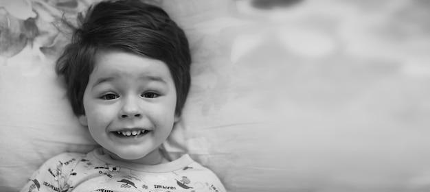 Foto em preto e branco retrato de uma criança deitada no travesseiro