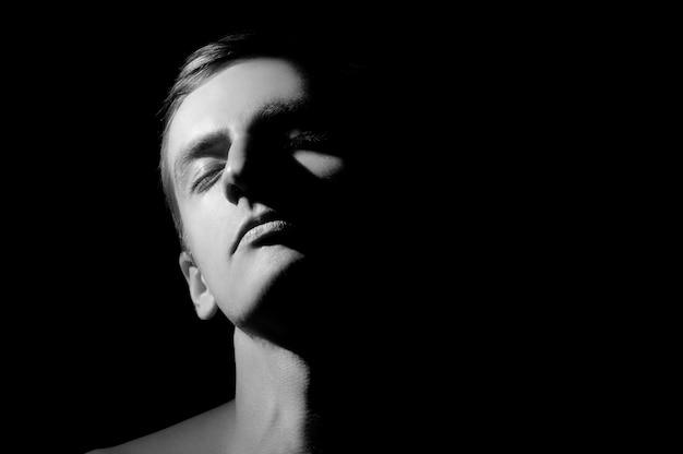Foto em preto e branco, retrato grande com metade do rosto acesa