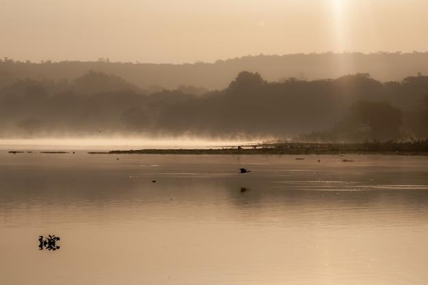 Foto em sépia da água do lago cercada por árvores e montanhas