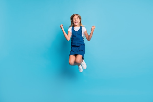 Foto em tamanho grande da garota legal hooray pulando grito usar sapatos de camiseta isolados em um fundo de cor azul pastel