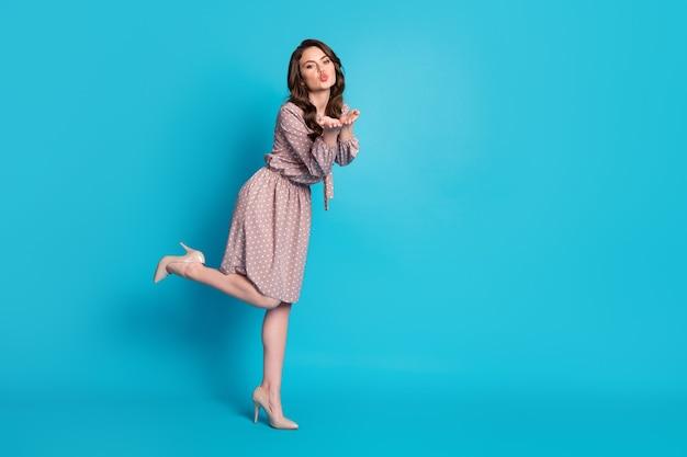 Foto em tamanho grande da linda doce linda garota aproveite a data do dia dos namorados mande beijo no ar, use saia salto alto isolado sobre fundo de cor azul