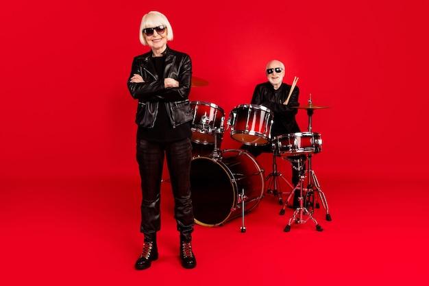 Foto em tamanho grande de duas pessoas, branco, cabelos grisalhos, aposentado, aposentado, mulher, mãos cruzadas, prontas para o evento da turnê de música rock, usar botas de jaqueta de couro isoladas sobre fundo de cor brilhante