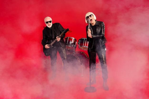 Foto em tamanho grande de funky duas pessoas grupo de banda de rock aposentado branco cabelo grisalho pensionista mulher vocalista cantar solo homem tocar guitarra baixo com fan tour isolado brilho brilhante cor vermelha fundo