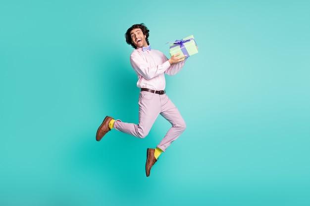 Foto em tamanho grande de jovem com cabelo castanho feliz pulando segurar presente usando roupa formal isolada no fundo azul-petróleo
