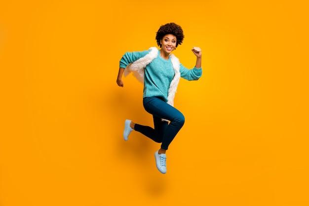 Foto em tamanho grande de uma garota afro-americana louca e divertida, pule, corra, use pressa, use um suéter branco turquesa azul outono roupa elegante e elegante isolada sobre a parede de cor amarela