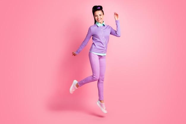 Foto em tamanho grande de uma garota encantadora pulando isolada sobre um fundo rosa pastel usando roupa violeta