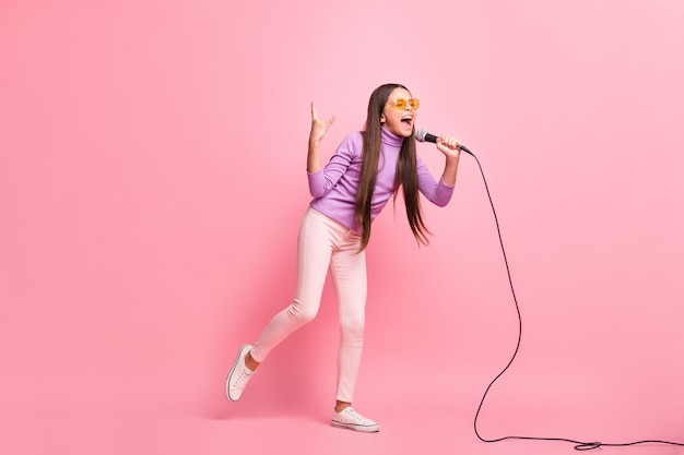 Foto em tamanho grande de uma garotinha louca cantando uma música no microfone mostrando um sinal com chifres isolado sobre um fundo de cor pastel