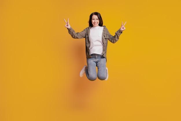 Foto em tamanho grande de uma jovem mulher pulando o sinal v isolado em um fundo amarelo