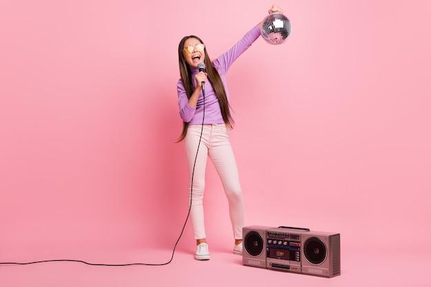Foto em tamanho real da garotinha cantando música microfone segurando bola de discoteca com caixa de som retro isolada em fundo de cor pastel