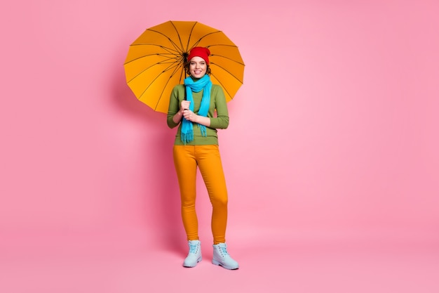Foto em tamanho real de alegre adorável linda garota bonita, aproveite a tempestade, viagem, férias, segure guarda-chuva brilhante, use jumper de roupa estilo casual isolado sobre a parede cor de rosa
