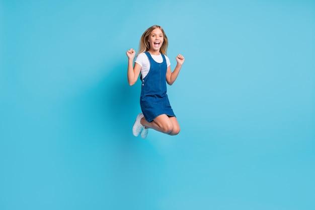 Foto em tamanho real de hooray garota loira engraçada pulando de tênis com vestido de camiseta e grito, isolado em um fundo de cor azul pastel