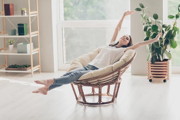 Foto em tamanho real de menina positiva sentada em uma cadeira de vime com braços esticados e vestindo roupas de estilo casual descalça em casa dentro de casa