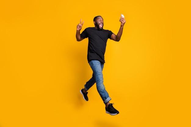 Foto em tamanho real de um cara afro-americano engraçado, louco, com uma jornada, um sinal de v, uma selfie, uma caminhada, um vídeo, um salto, um salto, uma camiseta jeans, uma parede amarela isolada.