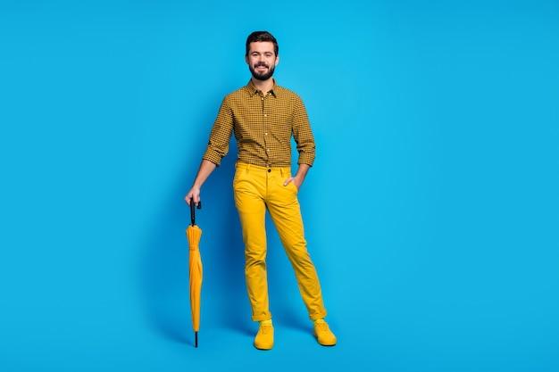 Foto em tamanho real de um cara sonhador imponente e sincero, aproveite o tempo livre, descanse, relaxe, use guarda-chuva brilhante, use roupas modernas e tênis bonitos isolados sobre a cor azul