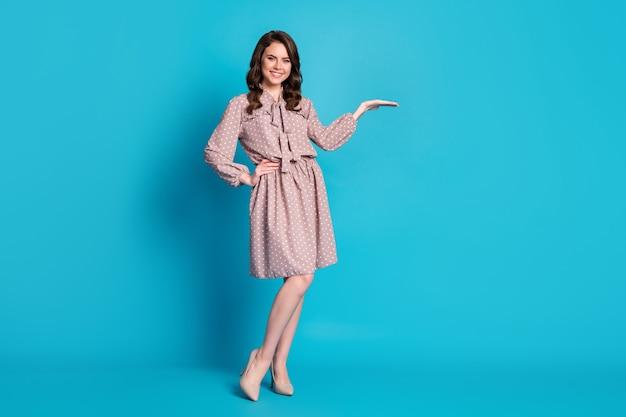Foto em tamanho real de um promotor positivo de menina alegre segurando a mão para indicar que os anúncios de vendas usam sapatos de saia de boa aparência isolados sobre um fundo de cor azul