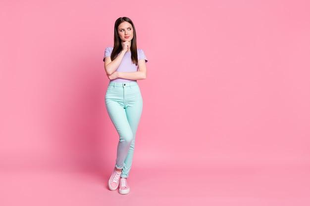 Foto em tamanho real de uma atraente senhora magra charmosa bom humor olhar para cima espaço vazio criativo pessoa inteligente usar camiseta violeta casual calça azul-petróleo sapatos isolado rosa cor pastel