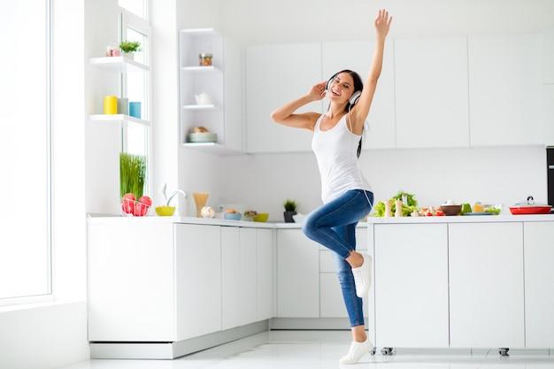 Foto em tamanho real de uma garota divertida e positiva em um clubber real descansando e ouvindo música estéreo melodia através de um fone de ouvido na cozinha, onde ela prepara o jantar de pratos de saúde em casa dentro de casa