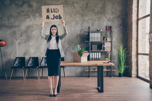 Foto em tamanho real de uma garota estressada e deprimida tendo problemas com a procura de emprego perder a ocupação crise empresa falida mostrar texto em papelão usar terno de salto alto no local de trabalho estação de trabalho
