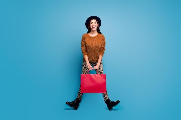 Foto em tamanho real de uma garota louca e divertida aproveite o outono primavera feriado caminhar compras segurar sacolas gritar usar suéter marrom estilo retro vintage calças botas chapéu isolado sobre a parede de cor azul