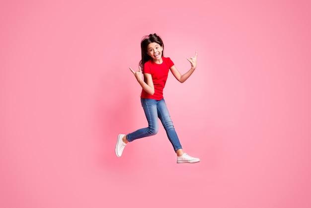 Foto em tamanho real de uma garota maluca salto show com chifres de símbolo vestindo uma camiseta jeans vermelha isolada sobre um fundo de cor pastel