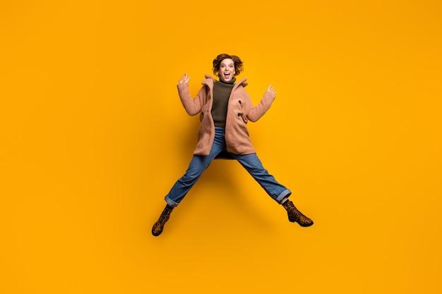 Foto em tamanho real de uma linda senhora descolada, pula alto, surpresa, férias, comece a se alegrar com as pernas abertas, use sapatos casuais jeans de leopardo com casaco rosa