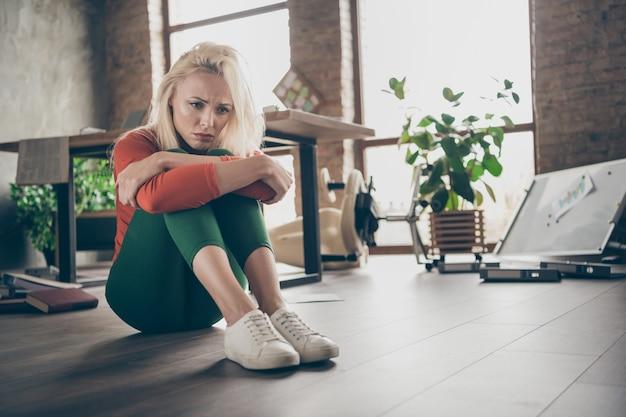 Foto em tamanho real de uma mulher ceo chateada, demitida, sente-se no chão, sente solidão e tenha problemas de inicialização do trabalho da empresa em um escritório bagunçado, vestindo calças verdes de gola alta vermelha