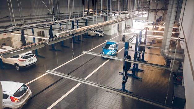 Foto em tons da estação de manutenção de automóveis automotivos com várias ferramentas e elevadores para conserto de automóveis