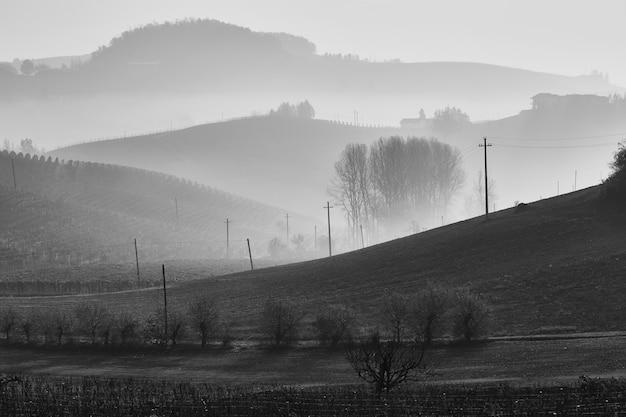 Foto em tons de cinza de belas colinas com neblina