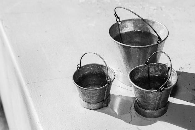 Foto em tons de cinza de diferentes tamanhos de baldes de metal