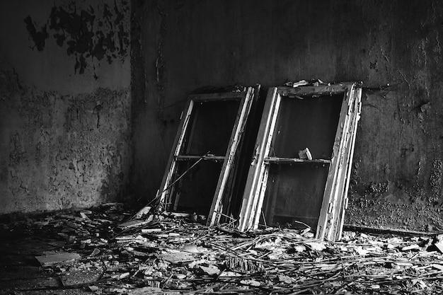 Foto em tons de cinza de molduras de janelas colocadas em um chão bagunçado em uma casa velha