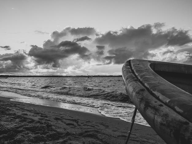 Foto em tons de cinza de um barco em uma praia com grandes ondas