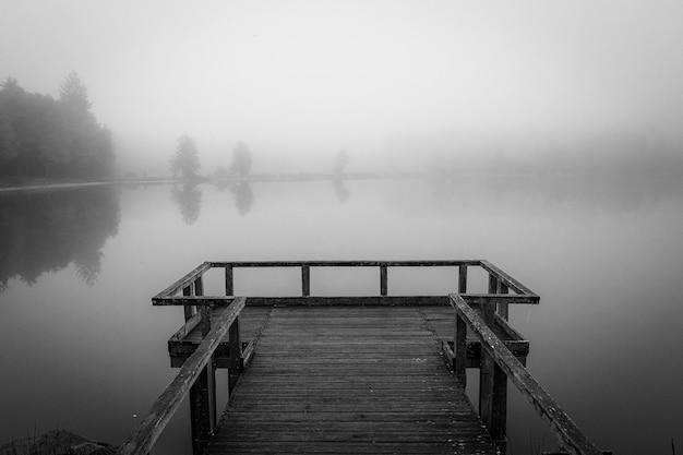 Foto em tons de cinza de um cais de madeira perto do mar, cercado por árvores cobertas de névoa