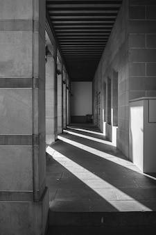 Foto em tons de cinza de um corredor externo com sombras de vigas