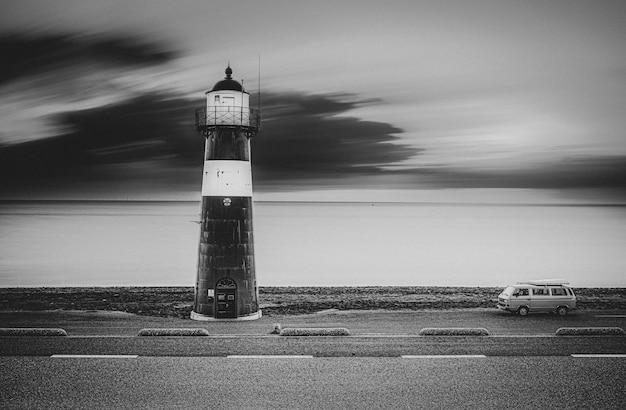 Foto em tons de cinza de um farol na estrada com uma van na lateral e o mar na