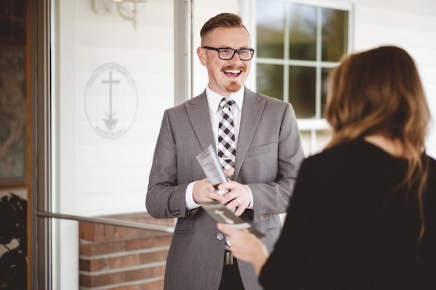 Foto em tons de cinza de um homem de terno cumprimentando e dando as boas-vindas a uma mulher vestindo uma camisa preta