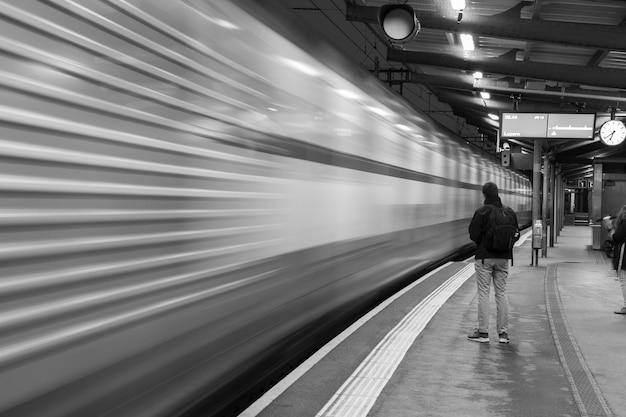 Foto em tons de cinza de um homem esperando um trem na estação e um trem borrado em movimento